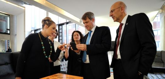 Universities Chris Skidmore MP, centre, tests out an augmented reality plinth during a visit to Manchester Metropolitan University accompanied by the University's Vice-Chancellor Professor Malcolm Press, right